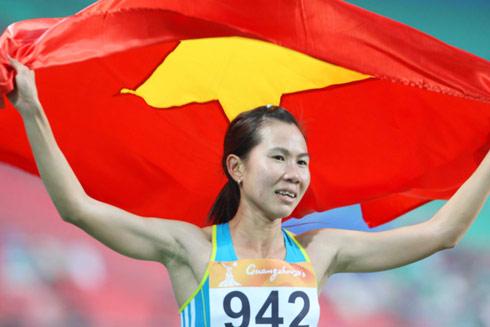 Trương Thanh Hằng vui mừng với tấm huy chương lịch sử. Cô chỉ về sau VĐV người Bahrain gốc châu Phi từng ba lần vô địch thế giới. Ảnh: A.T.
