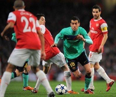 Tiền vệ Busquets (áo xanh, bên phải) trong vòng vây của Arsenal.