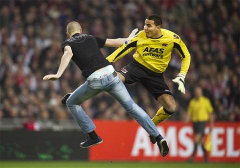 Alvarado (áo vàng) né đòn và đánh trả hooligan của Ajax.