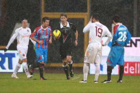 Trọng tài Tagliavento cho hoãn trận đấu sau khi hội ý với hai đội. Ảnh: AFP.